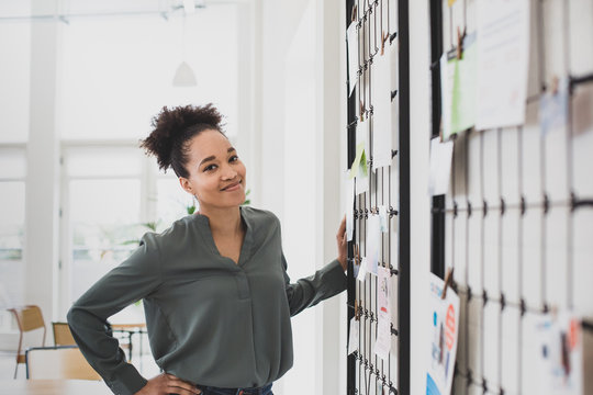 Portrait of African American businesswoman next to noticeboard