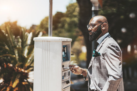 An adult confident bald black manentrepreneur with a beard and in spectacles is using a parking pay station outdoors; an African businessman is inserting his bank card in a parking payment terminal