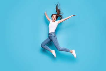 Full body photo of lovely girl raising hands arms jumping screaming isolated over blue background