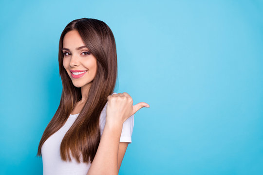 Close up photo of pretty youth showing advertisement on copy space smiling wearing white t-shirt isolated over blue background