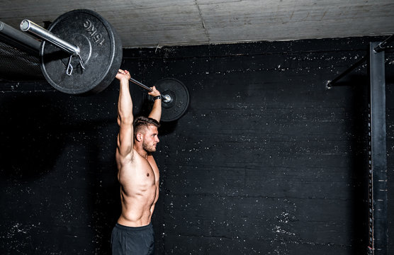 Young muscular sweaty man with big muscles doing barbell weight training workout in the gym dark image