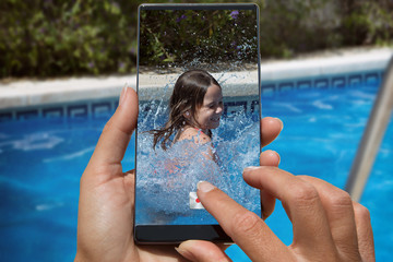 Woman photographing on cell phone happy little girl in pool.