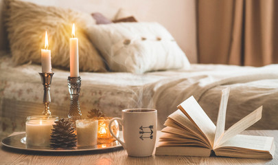 Book, cup of coffee and many candles on the home background.  Home and home decor. Candles flame. HOME concept