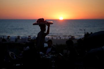 A vendor sells candied apples during the sunset on the beach in Gaza City