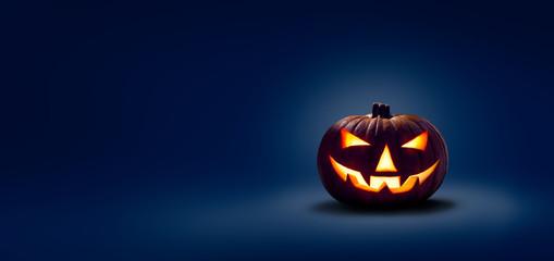 Fototapeta A halloween lit Jack O Lantern in a spotlight glow on a wide dark blue background obraz