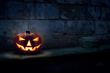 A single halloween Jack O Lantern on the left side of a dark blue night stone plinth with light shinning down on it