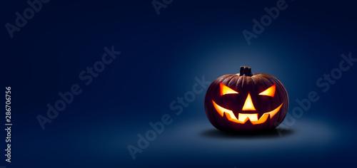 A halloween lit Jack O Lantern in a spotlight glow on a wide dark blue background
