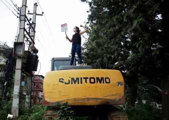 """An activist holding a placard that reads """"where is socialism for the road"""", stands atop of a vehicle in front of the marked trees which will be cut down for road expansion during a protest against the unplanned urbanization in Kathmandu"""