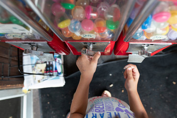 Child Placing a Quarter in Arcade Vending Machine