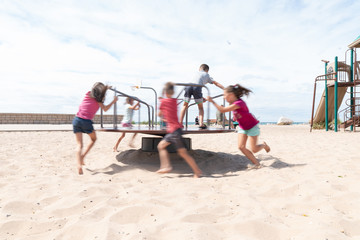 Children Playing on Merry Go Round at a Beach