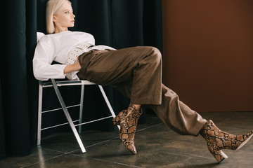 stylish blonde woman in white blouse and boots with snakeskin print sitting on chair near curtain on brown Wall mural