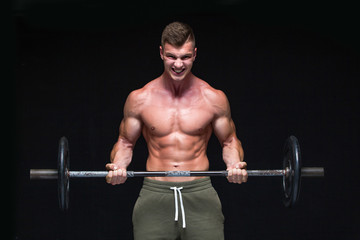 Muscular man working out in studio doing exercises with barbell at biceps, strong male naked torso...