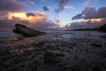Cloudy Twilight on a Rocky Beach
