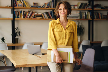 Young beautiful woman in yellow shirt leaning on desk with notepad and papers in hand while happily looking in camera in modern office