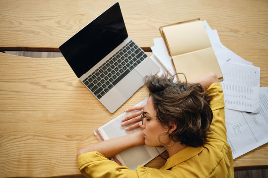 Top view of young tired woman asleep on desk with laptop and documents under head at workplace
