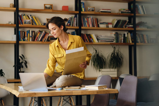 Young attractive smiling woman in yellow shirt sitting on desk with papers while dreamily working on laptop in modern office