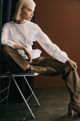 stylish blonde woman in white blouse and boots with snakeskin print sitting on chair near curtain...