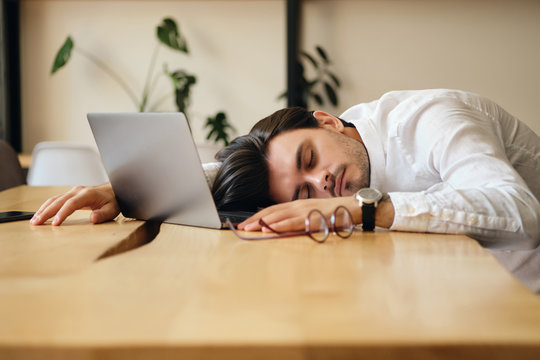 Young tired man with laptop sleeping on desk at work in office