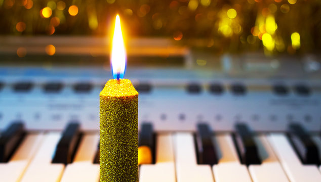 Decorative candle near the piano on the background of Christmas garlands. Merry Christmas music_