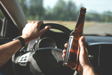 Driver is driving a car with a bottle of beer in hand. Drunk driving concept.
