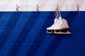 Figure skates hanging over gradient blue wall in locker room with copy space