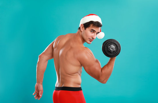 Sexy shirtless Santa Claus with dumbbell on blue background