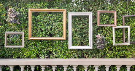 Empty picture frames on green leaves wall