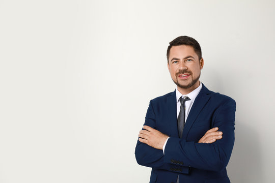 Portrait of handsome man in suit on light background. Space for text