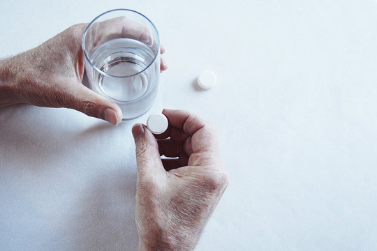 Elderly man hands taking medicine pill with a glass of water