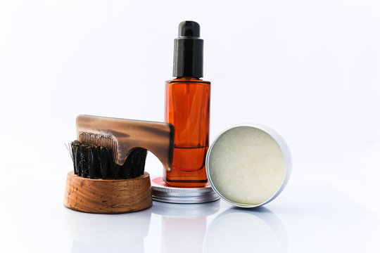 A selection of men's beard grooming products that include oil, wax and a brush, shot against a clean white background