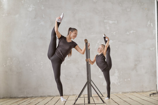 Graceful little girl ballerina standing on hands and stretching with teacher in dance studio