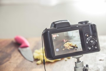 Camera shooting a photo of chopped potatoes on a wooden surface with a knife on the side