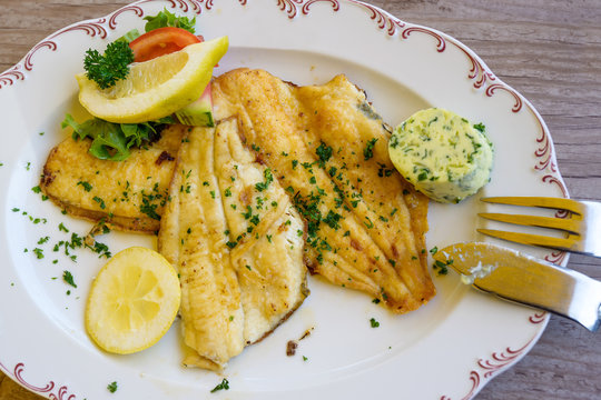 fried plaice fillet with herb butter and lemon on a plate, typical food in northern germany at the coast, high angle view, above