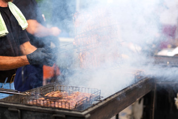 The cook fries juicy steaming meat on a charcoal grill. Food and cooking equipment at a street food festival Wall mural