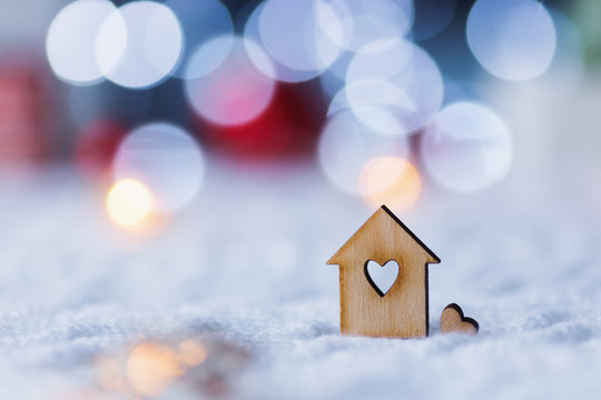 Wooden icon of house with hole in form of heart with red home Christmas decor and blurred bokeh background in daylight.