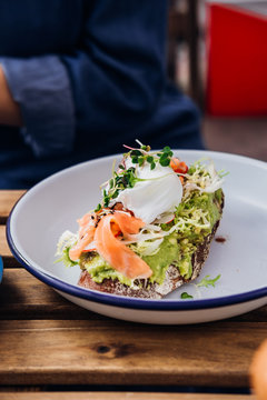 Avocado toast with smoked salmon and poached egg at hipster coffee shop