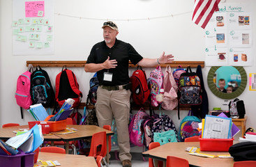 Joe Emery, TAC*ONE trainer and former Las Vegas police department sergeant, speaks to kindergarten students, some seen in mirror at right, at Pinnacle Charter School during TAC*ONE training for an active shooter situation in a school in Thornton