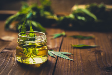 Foto op Aluminium Spa Glass jar with hemp oil and fresh leaves on wooden background