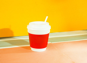 Wall Mural - Red coffee cup yellow background.Modern concept