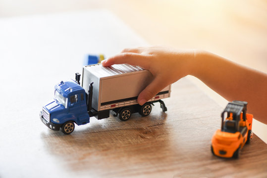 child boy playing toys on table at home - kid hands playing toy car truck