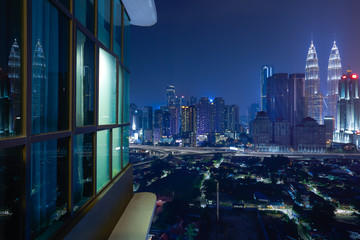 Fotomurales - Night view of a beautiful cityscape with window reflection