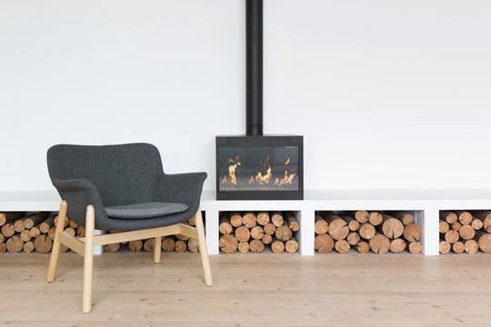 Cozy minimalistic interior with fireplace in a bright room with a woodpile and an armchair
