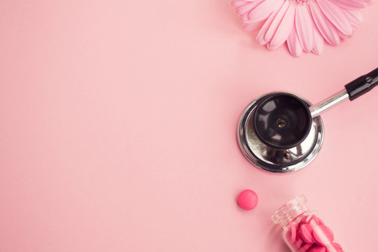 Women's health, medicine and healthcare concept. Pink pills in a glass bottle, a medical stethoscope and a flower on a light background. Copy space