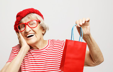 Lifestyle, holiday and people concept: elderly woman with gift bag.