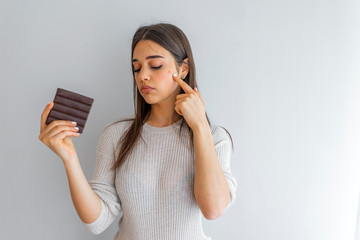 Young woman with acne problem holding chocolate bar on grey background. Skin allergy. Closeup Acne Problem Face Woman Eating Chocolate bar. Skin allergy. Concept of skin problems