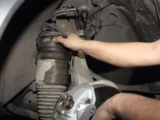 Close up hands of car mechanic remove the front suspension rack, repair the air spring of the car