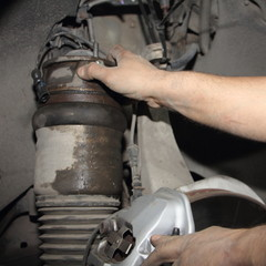 Close up hands of car mechanic fitting the pneumatic cylinder of front suspension rack, repair the air spring of the car