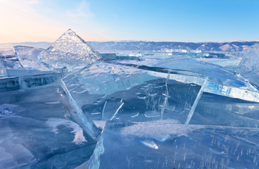 Winter landscape of the frozen Baikal Lake. Fields of ice hummocks with transparent ice blocks on the Small Sea Strait at sunset. Cold natural background