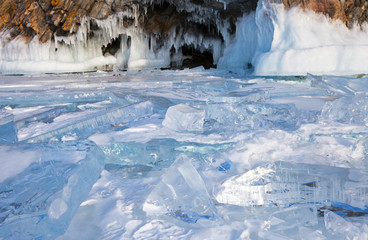 Baikal Lake in February cold day. A hummock of transparent blue ice near an ice cave in the Harantsy Island. Winter travel around the island of Olkhon