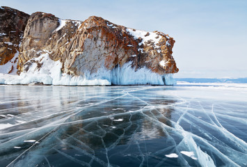 Beautiful winter landscape of the frozen Baikal Lake. Endless fields of blue slippery ice with cracks near the red rocks of Olkhon Island. View on the Strait of Small Sea on a sunny cold day